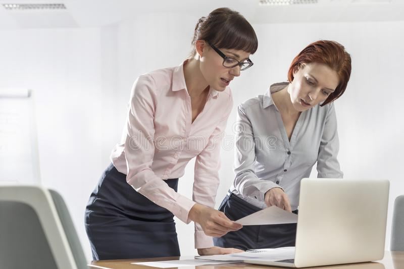 Colegas del negocio que discuten sobre documentos en el escritorio en oficina imagenes de archivo