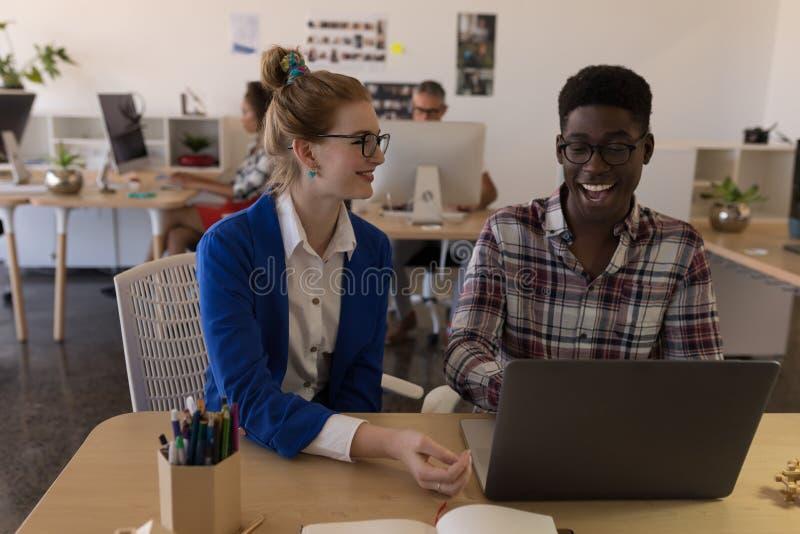 Colegas del negocio que discuten sobre el ordenador portátil en oficina imagen de archivo libre de regalías
