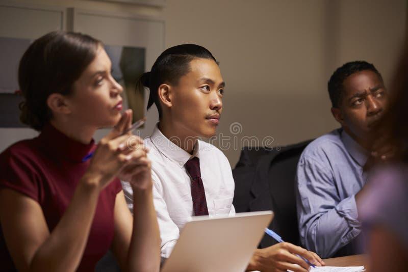 Colegas del negocio que escuchan en la reunión de la tarde, cierre para arriba imagen de archivo
