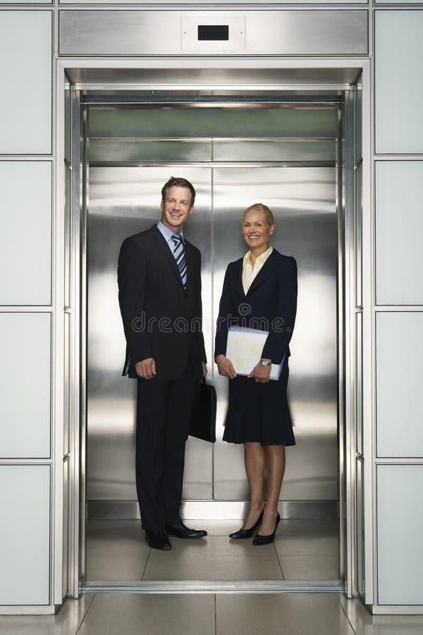 Colegas del negocio que se colocan en elevador fotos de archivo