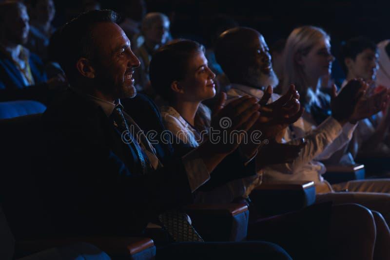 Colegas del negocio que sientan y que miran la presentación con la audiencia y manos que aplauden imagenes de archivo