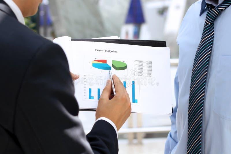 Colegas del negocio que trabajan junto y que analizan el higo financiero imagen de archivo