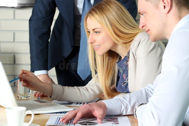 Colegas del negocio que trabajan junto y que analizan figuras financieras en un ordenador portátil foto de archivo