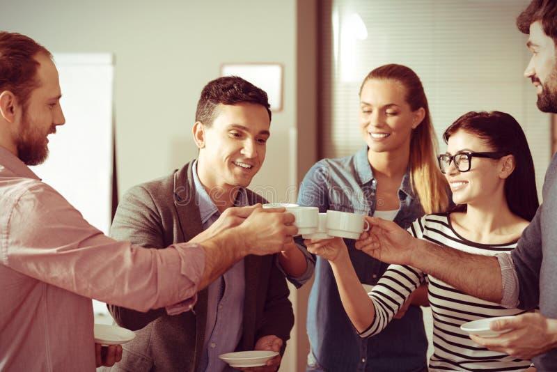 Colegas deleitados felizes que guardam copos de café imagens de stock royalty free