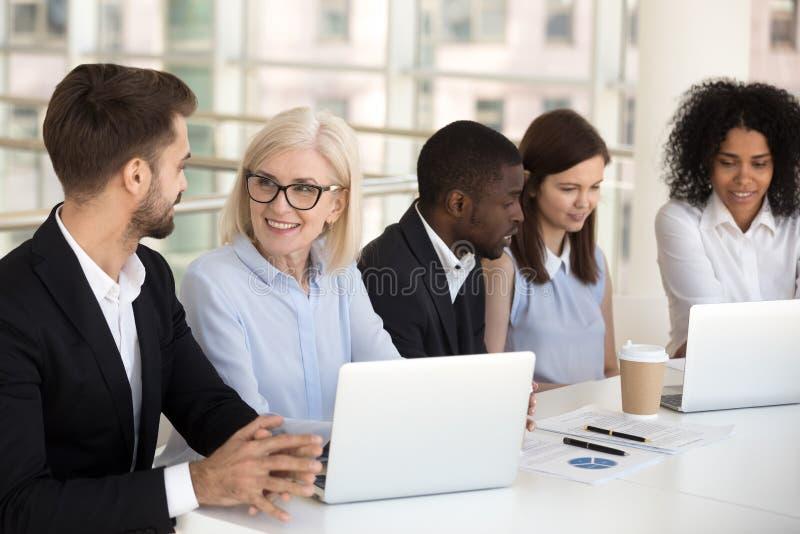 Colegas diversos de sorriso que trabalham junto no portátil na sala de reuniões imagens de stock royalty free
