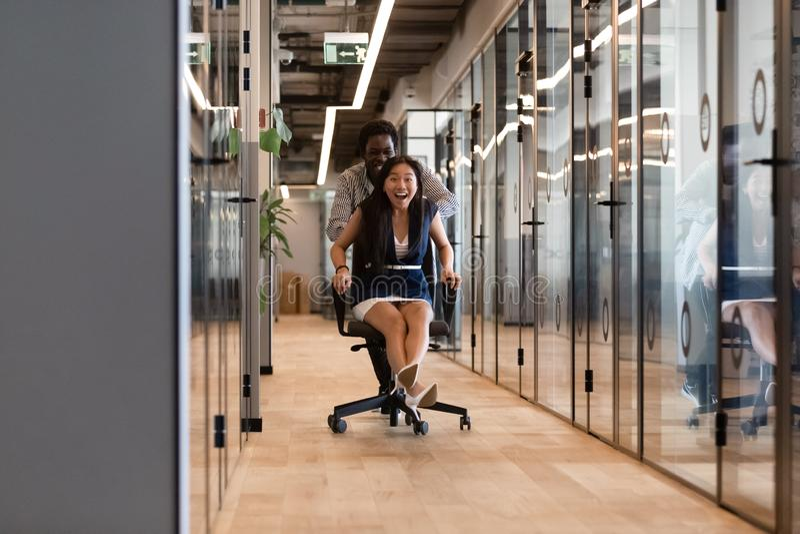 Colegas diversos emocionados que ríen el montar a caballo en silla en vestíbulo de la oficina imagen de archivo libre de regalías