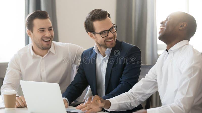 Colegas diversos felices de los hombres de negocios que hablan riéndose de la broma que trabaja junto imagen de archivo