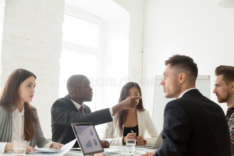 Colegas diversos que disputam durante a reunião do trabalho imagens de stock