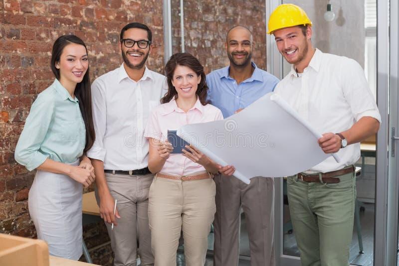 Colegas do arquiteto que trabalham em modelos e na tabuleta digital imagens de stock royalty free