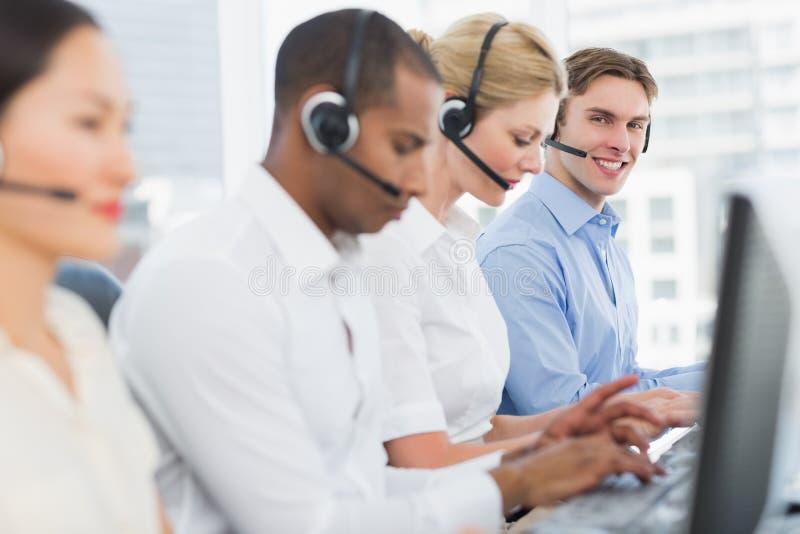 Colegas do negócio com auriculares usando computadores na mesa fotos de stock