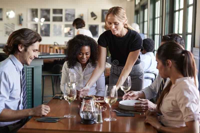 Colegas do negócio de Serving Meal To da empregada de mesa que sentam-se em torno da tabela do restaurante imagem de stock royalty free