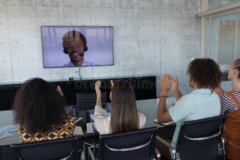 Colegas do negócio que aplaudem ao atender a uma chamada video em uma sala de conferências imagens de stock royalty free