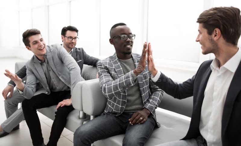 Colegas do negócio que dão-se uns cinco altos ao sentar-se na entrada do escritório fotos de stock