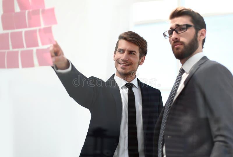 Colegas do negócio que discutem etiqueta-notas na placa do escritório foto de stock royalty free