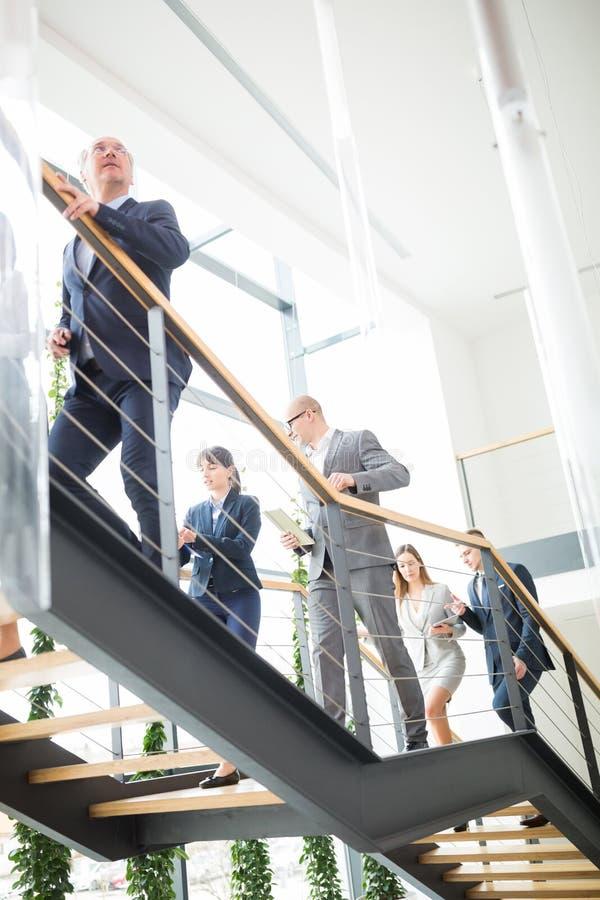 Colegas do negócio que escalam escadas no escritório moderno foto de stock royalty free