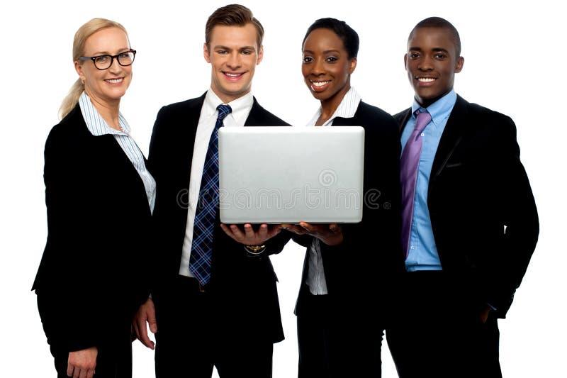 Colegas do negócio que prestam atenção ao vídeo no portátil foto de stock royalty free