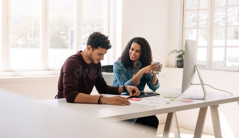 Colegas do negócio que sentam-se junto na tabela e que discutem fotografia de stock royalty free