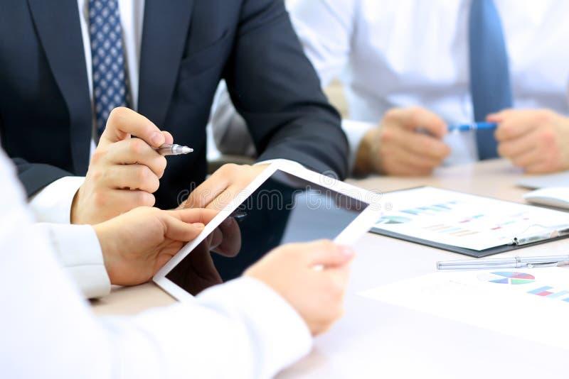 Colegas do negócio que trabalham e que analisam gráficos financeiros em uma tabuleta digital imagem de stock