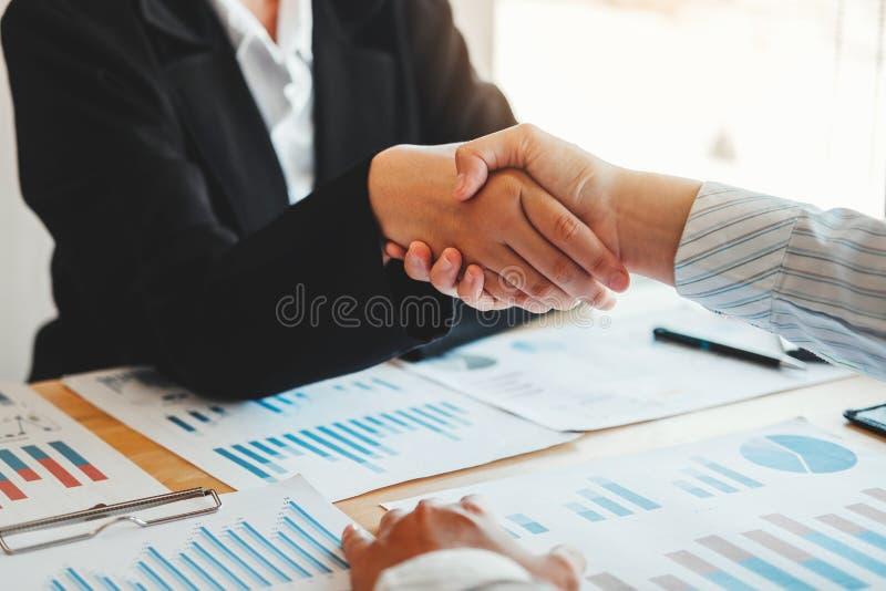 Colegas do sócio comercial que agitam as mãos que encontram a finança do plano do projeto da partida e o gráfico novos da economi foto de stock royalty free