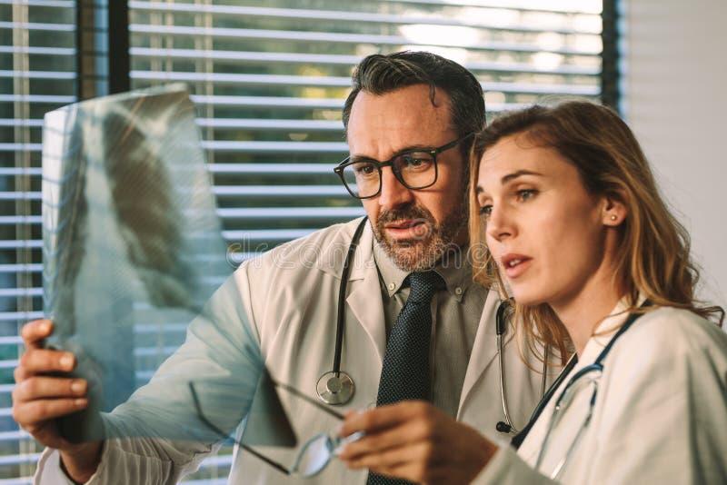Colegas dos doutores que olham o filme de raio X junto imagem de stock
