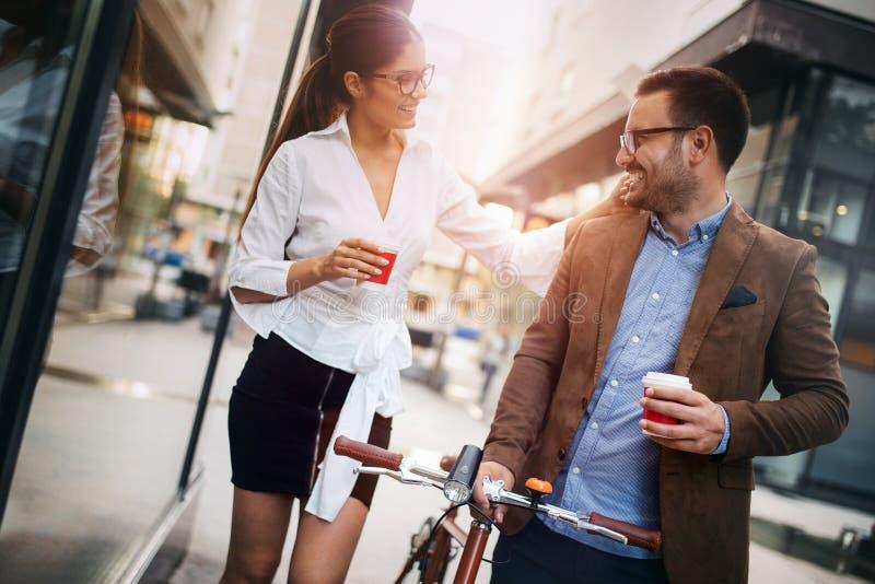 Colegas felices del negocio que hablan y que caminan en la ciudad al aire libre imagenes de archivo