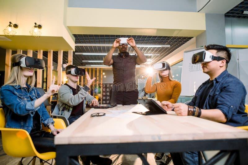 Colegas felices que prueban los vidrios del vr interiores Realidad virtual y concepto usable de la tecnología con la gente joven  foto de archivo