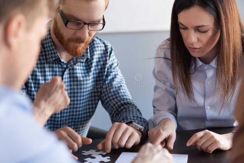 Colegas focalizados que montam o enigma de serra de vaivém durante a reunião imagem de stock royalty free