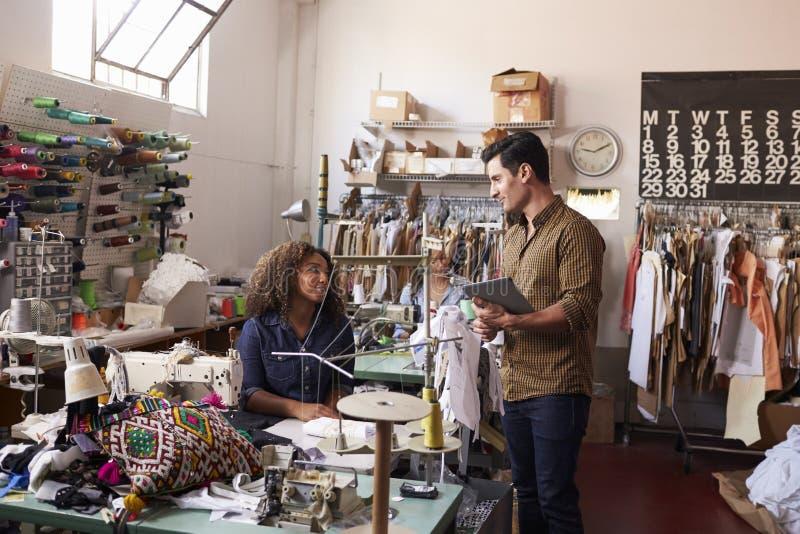 Colegas hablando en la ropa que fabrica el taller imagen de archivo libre de regalías