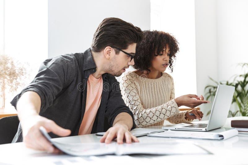 Colegas jovenes concentrados que usan el ordenador portátil imagen de archivo
