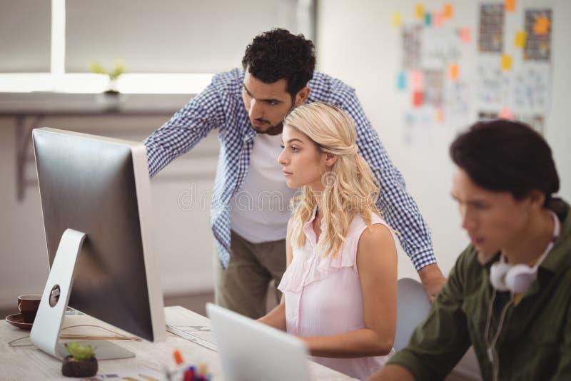 Colegas jovenes del negocio que trabajan en PC de sobremesa en el escritorio de oficina foto de archivo libre de regalías