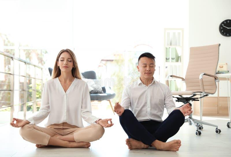 Colegas jovenes que hacen yoga en oficina foto de archivo libre de regalías