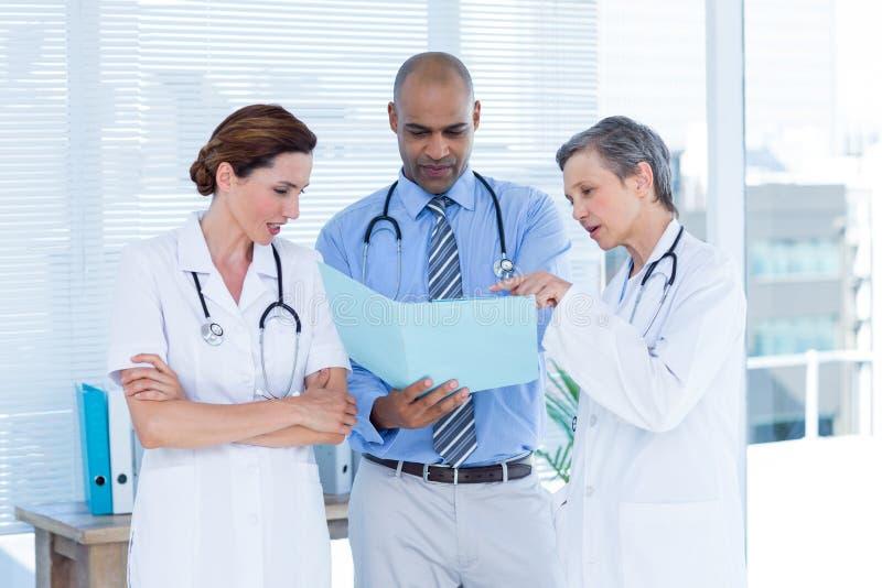 Colegas médicos concentrados que analizan el fichero junto foto de archivo