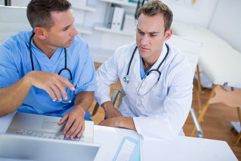 Colegas médicos concentrados que discutem e que trabalham com portátil foto de stock royalty free