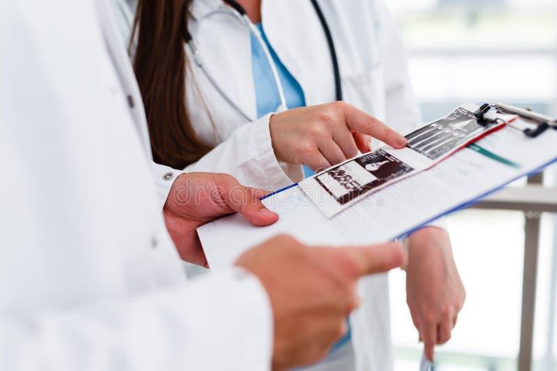 Colegas médicos jovenes que analizan datos sobre el cartón fotografía de archivo
