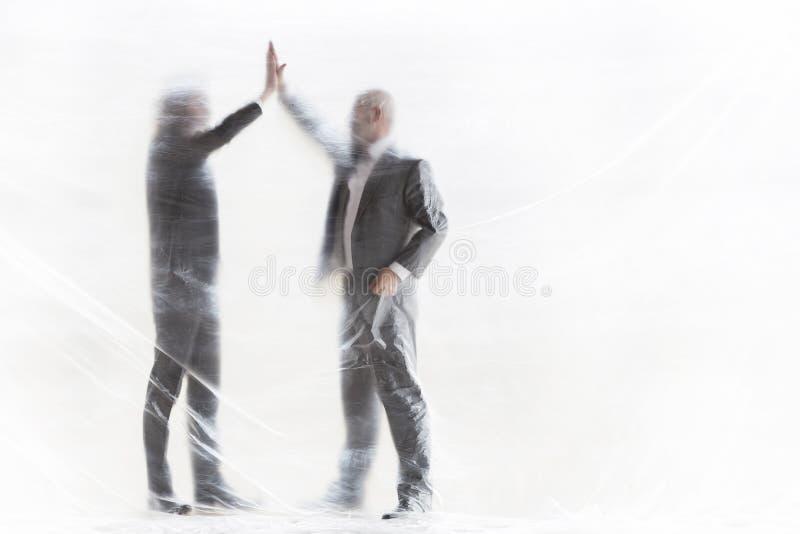 Colegas masculinos acertados que dan el alto-cinco rato cubierto de plástico en la oficina fotografía de archivo
