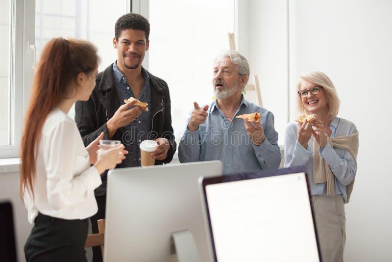 Colegas mayores y jovenes que hablan mientras que come la pizza en oficina fotografía de archivo