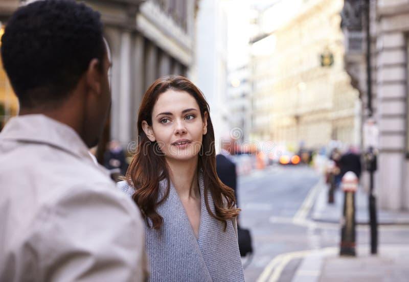 Colegas milenarios del negocio que se levantan en una calle en Londres que tiene una conversación, cierre imágenes de archivo libres de regalías
