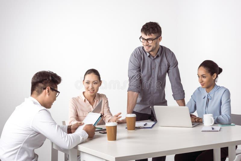 Colegas multiétnicos del negocio que trabajan con los dispositivos digitales y que hablan en la oficina imagen de archivo libre de regalías