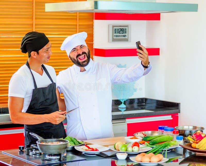 Colegas no trabalho: Cozinheiros chefe tailandeses e europeus em fazer da cozinha imagem de stock royalty free