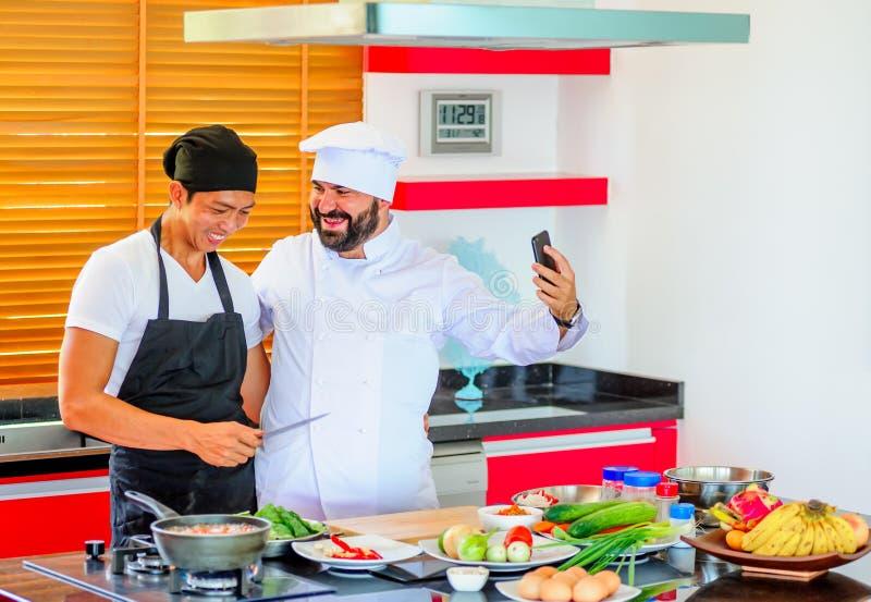 Colegas no trabalho: Cozinheiros chefe tailandeses e europeus em fazer da cozinha imagem de stock