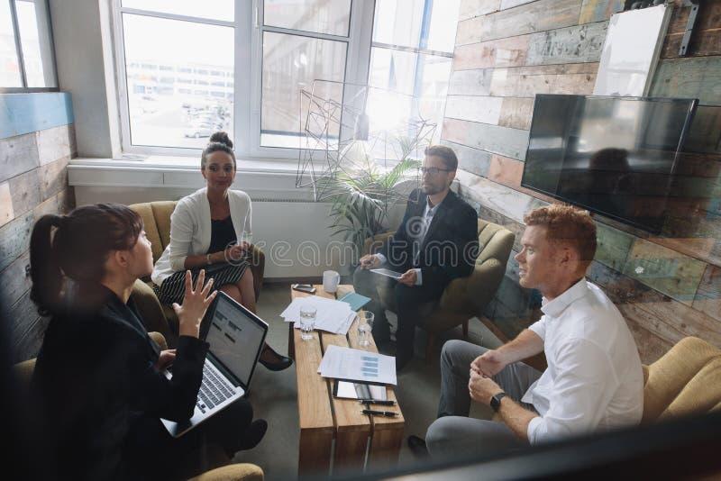 Colegas novos do negócio que encontram-se no escritório moderno foto de stock