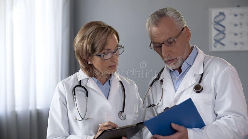 Colegas que comparam resultados, homem e doutores fêmeas que consultam no diagnóstico fotografia de stock