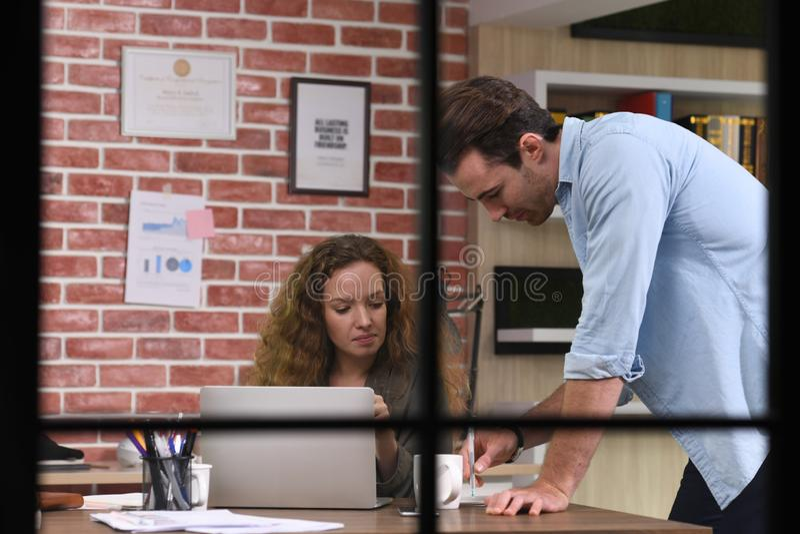 Colegas que discuten el trabajo usando un ordenador portátil en la oficina fotos de archivo