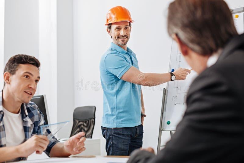 Colegas que escutam a apresentação de um construtor novo fotografia de stock