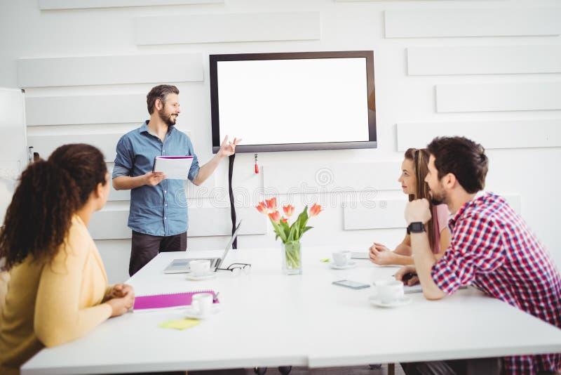 Colegas que escutam o executivo na reunião no escritório criativo fotografia de stock
