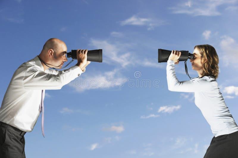 Colegas que miran uno a través de los prismáticos al aire libre imagenes de archivo