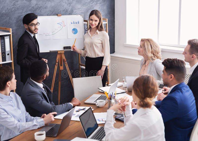 Colegas que mostram diagramas no flipboard no escritório imagem de stock royalty free