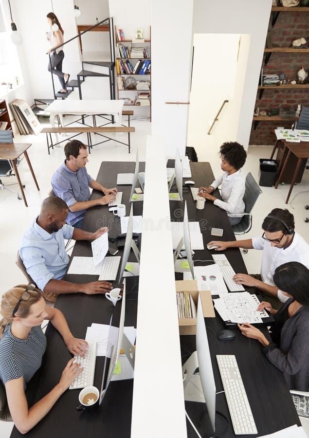 Colegas que trabalham em um escritório de plano aberto ocupado, vertical imagens de stock royalty free