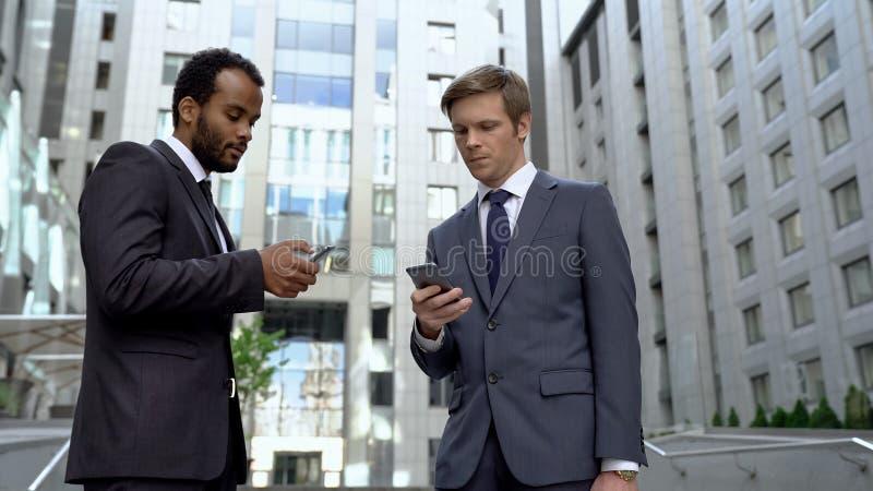 Colegas que usan los smartphones para la transacción conveniente del dinero del app de la actividad bancaria en línea foto de archivo libre de regalías