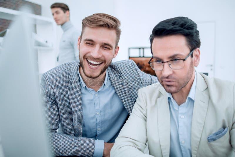 Colegas sonrientes que miran el monitor de computadora imágenes de archivo libres de regalías